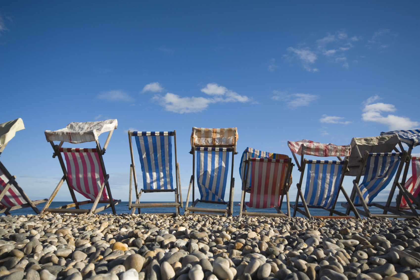 colourful striped deck chairs on a pebbled beach
